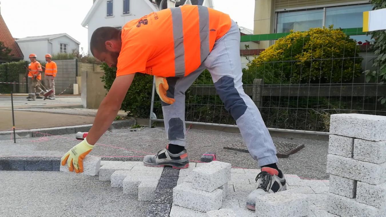 Un ouvrier en gilet orange pose les pavés coquillés à la main Avenue Foch à Wimereux.