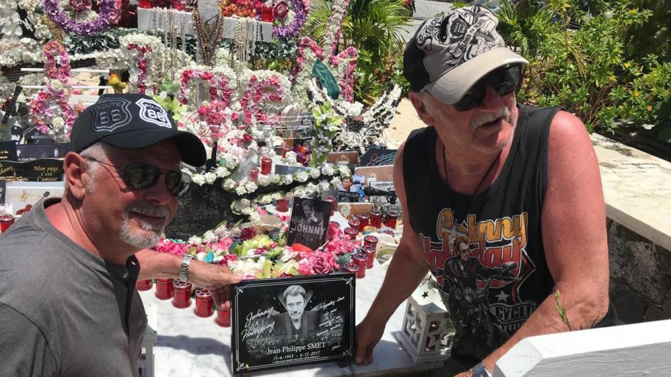 Des fans de Johnny posent avec la plaque sur la tombe du chanteur à Saint-Barthélémy. La tombe est recouverte d'objets commémoratifs.