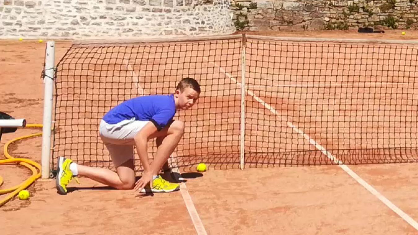 Arthur Daudruy, un jeune joueur de tennis, a le genou à terre au niveau du filet d'un terrain de tennis à Boulogne-sur-Mer en plein soleil.